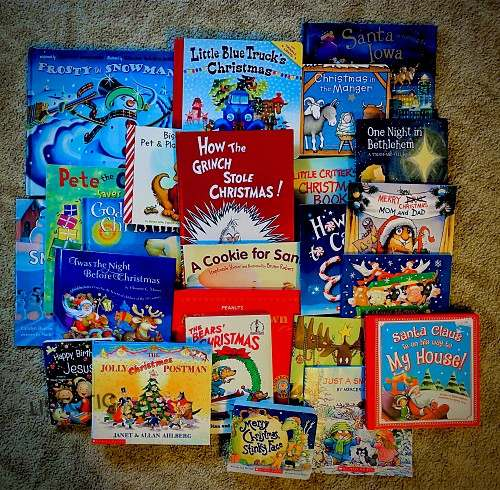 variety of Christmas books spread on the floor to be used for one of the elf on the shelf arrival ideas