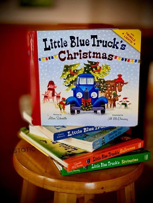 Hardcover little blue truck story book stacked on top of other published Little blue truck books