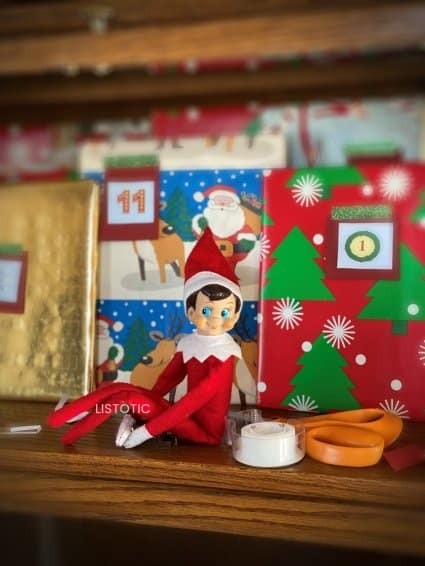 Elf on the shelf sitting with book advent calendar