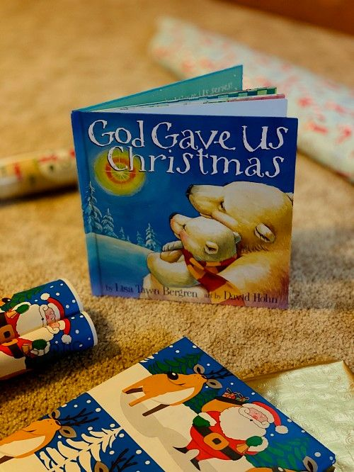 holiday wrapping paper and a children's story book propped up on the ground a Christmas bedtime stories book