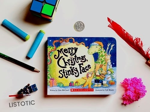 Merry Christmas Stinky Face book on a table top with random objects for Christmas bedtime stories