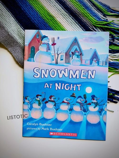Snowmen at night book on top of a scarf for Christmas stories read aloud