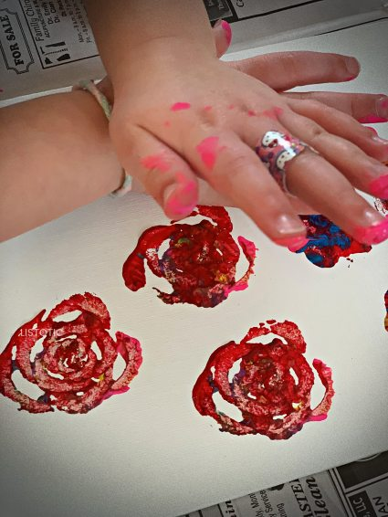 children's hands making a celery rose print with celery stamps