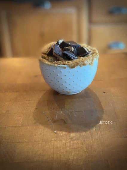 Peanut butter keto mug cake on wood counter ready to eat