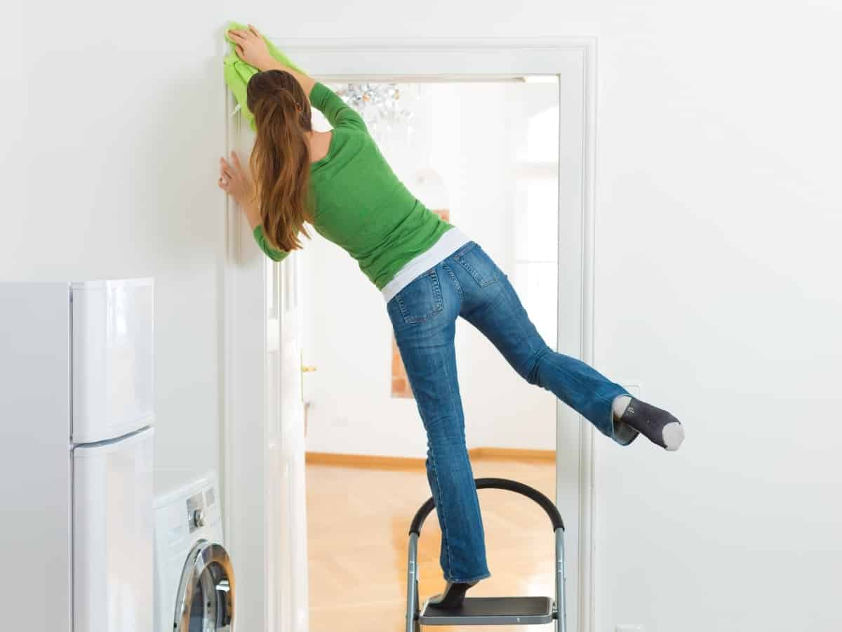 a woman on a ladder dusting on top of door frames
