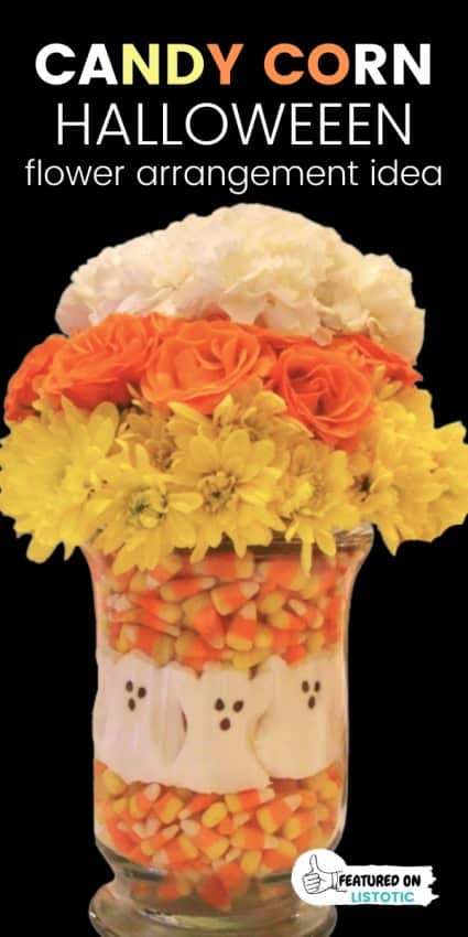 Halloween flower centerpiece with candy corn and white, yellow and orange flowers.